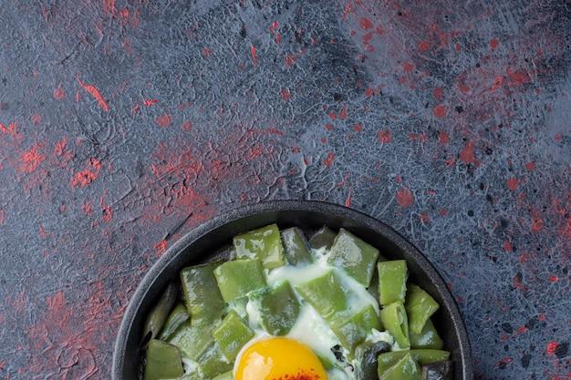 Зеленая фасоль, приготовленная с яйцом на сковороде.