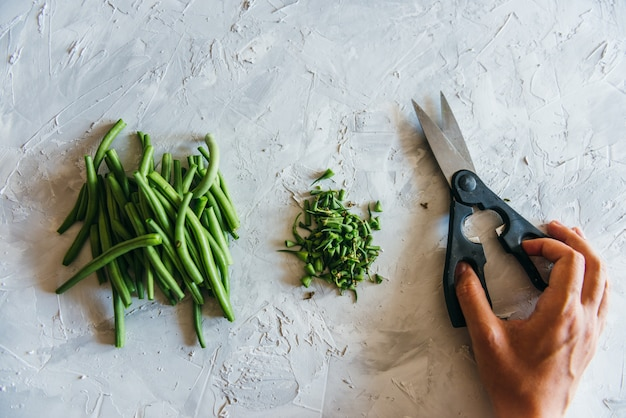 Green beans on a grey concrete background wooden board cutting with scissors