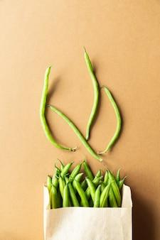 Зеленая фасоль в крафтовой упаковке на коричневом столе. собирайте органическую здоровую пищу