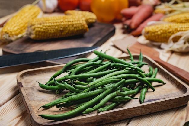皿のインゲンと台所のテーブルの他の野菜をクローズアップ