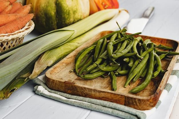 Зеленая фасоль в тарелке и другие овощи на кухонном столе