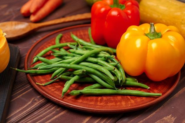 Зеленая фасоль в глиняной тарелке с овощами крупным планом