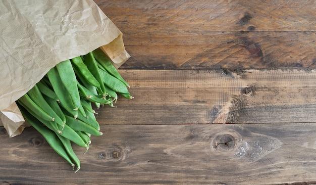 Зеленая фасоль в бумажном пакете на деревянной поверхности. скопируйте пространство. вид сверху.