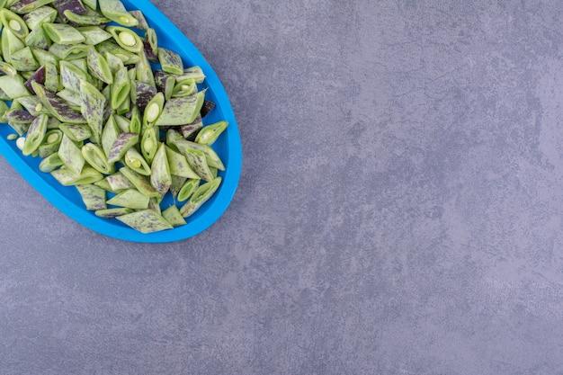 Fagiolini isolati in un vassoio di legno su superficie blu