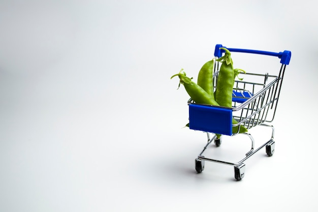 Green beans in mini shopping cart isolated on a white background
