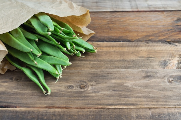 Green beans in paper bag on wooden surface. copy space. top view.