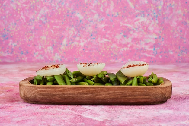 Insalata e spuntini dei fagiolini sul piatto di legno.