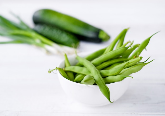 The green beans in white plate with green vegetables