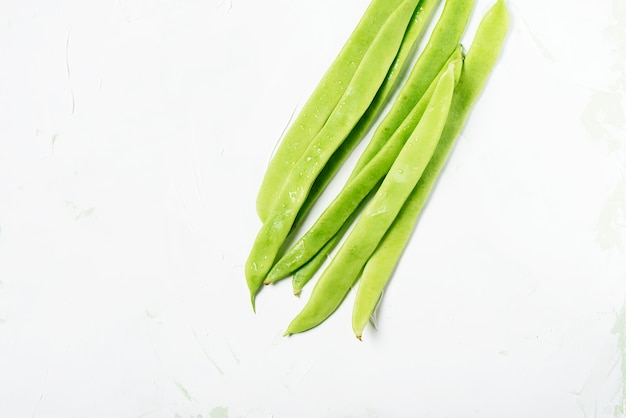 Green beans on the white stone background with copyspace