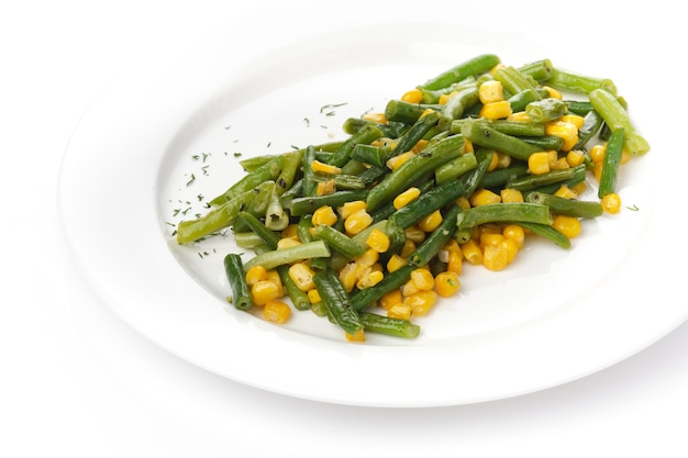 Green beans with corn on a white plate on a white bacgraund