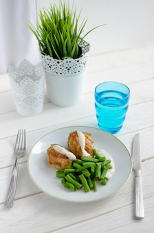 ローストチキンの胸肉とクリーミーなソースが美しく添えられたインゲン豆。