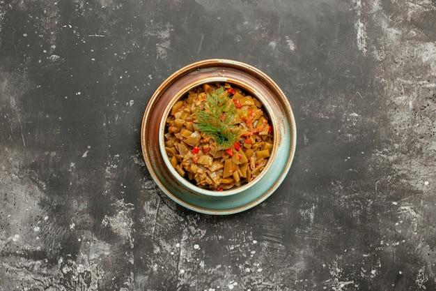 暗いテーブルのボウルにトマトとサヤインゲンを食欲をそそるトマトとサヤインゲン
