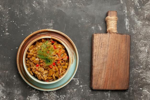 Стручковая фасоль с помидорами тарелка аппетитной стручковой фасоли с помидорами рядом с разделочной доской на столе