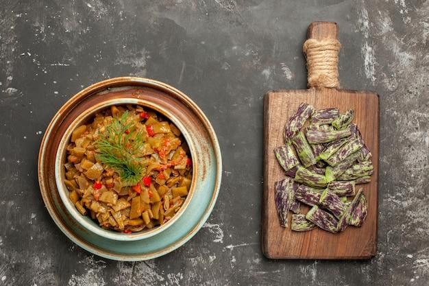 食欲をそそるトマトのトマトボウルとサヤインゲンとテーブルの上のまな板の横にあるサヤインゲン