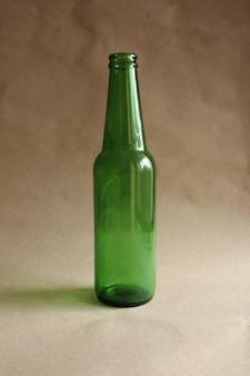 Green beer bottle on brown background