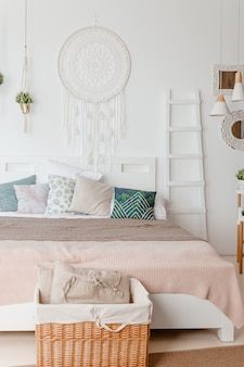 Green, beige pillow on bed in bedroom with pastel colored bedsheets on bed. stylish apartment design in lagom style.stylish scandinavian white interior with bed, tropical plant, cozy blanket.