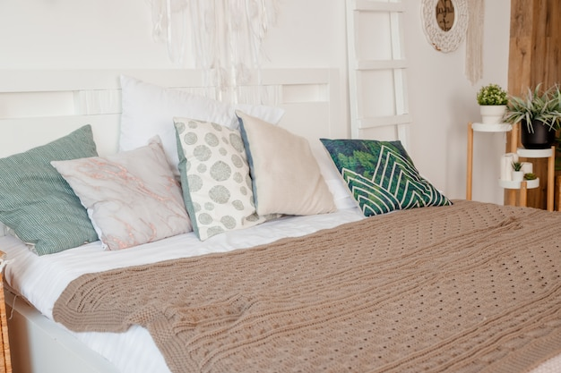 Зеленая, бежевая подушка на кровати в спальне с простынями в пастельных тонах на кровати. стильный дизайн квартиры в стиле лагом. стильный скандинавский белый интерьер с кроватью, тропическим растением, уютным одеялом.