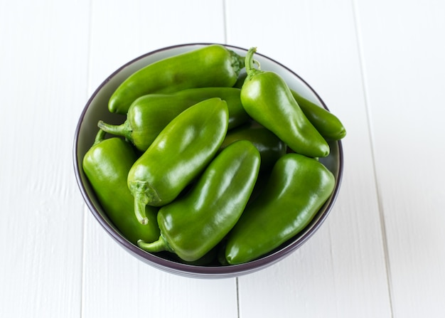 Green bell pepper in a bowl on a wooden table.