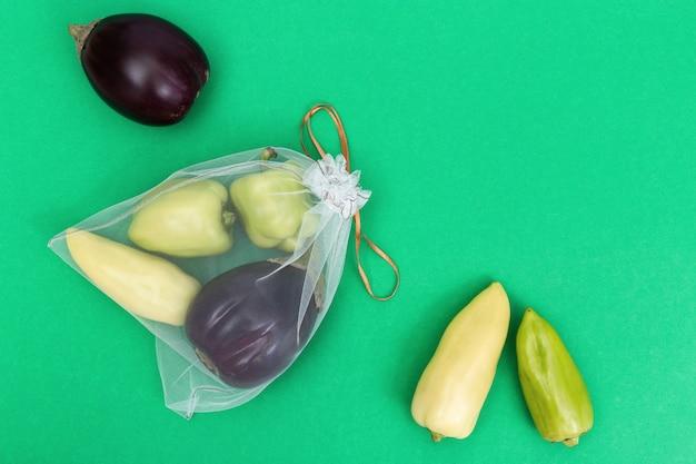 녹색 피망 그리고 녹색 종이 배경에 재사용 가능한 에코 가방에 가지. 음식 저장을 위해 투명 섬유에서 가방에 신선한 야채. 플라스틱 무료 개념. 평평하다. 평면도.