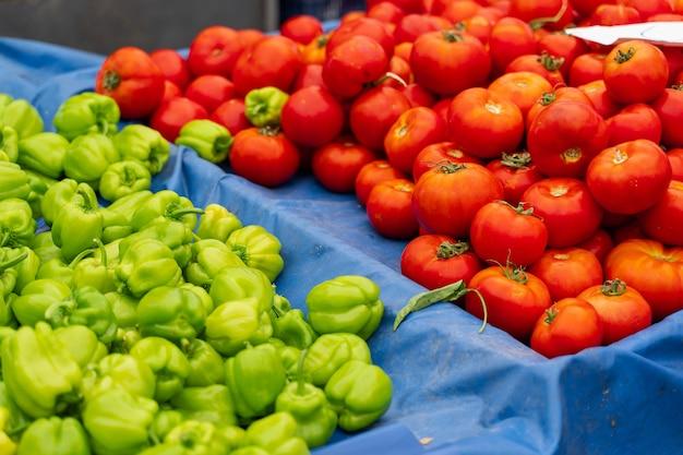 야채 시장에 녹색 피망과 토마토입니다.