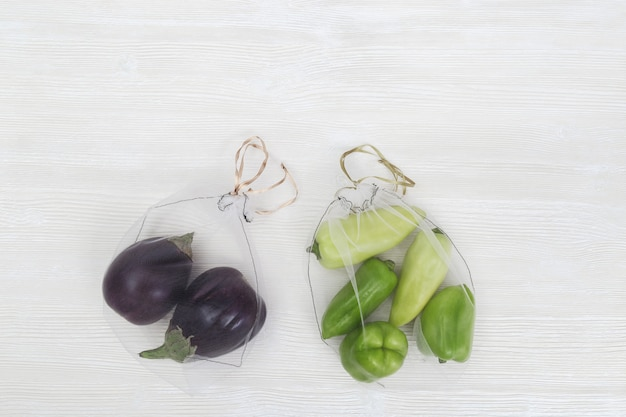 Green bell peppers and eggplants in reusable bags