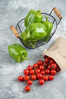 Зеленый болгарский перец в металлической корзине с помидорами черри внутри деревенской сумки на мраморном столе.