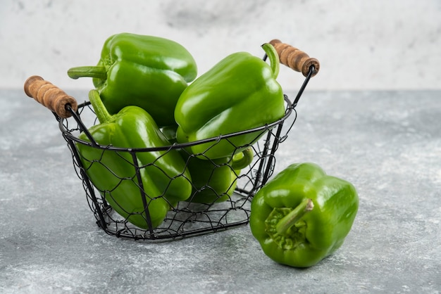 Green bell peppers in a metallic basket on marble table.