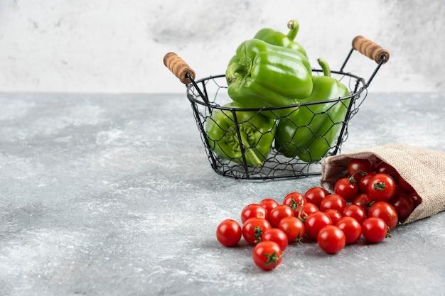 Peperoni verdi in un cesto metallico con pomodorini all'interno di un sacchetto rustico su un tavolo di marmo.