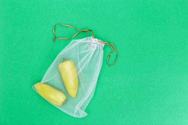 Green bell peppers in reusable eco bags on green,  plastic free concept.