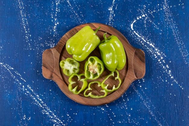 Peperoni verdi e anelli su tavola di legno su superficie di marmo