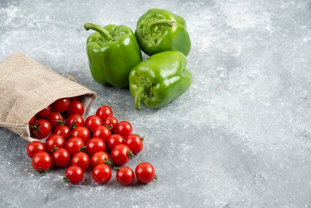 Green bell peppers with cherry tomatoes inside rustic bag on marble table.