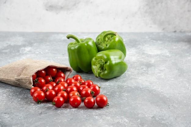 대리석 테이블에 소박한 가방 안에 체리 토마토와 녹색 피망.