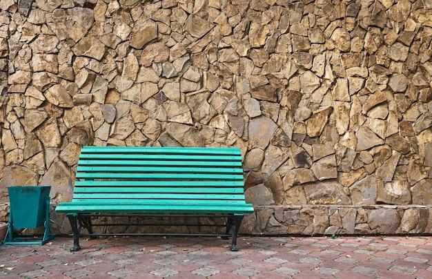 緑のベンチが野生の石の壁に立っています