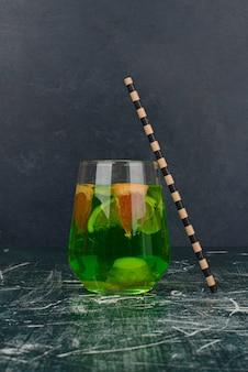 Зеленый напиток с лимоном и соломинкой