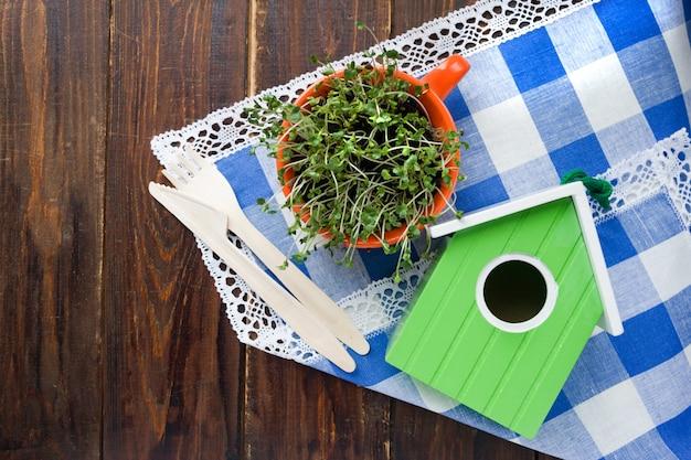 Зеленый скворечник, ростки мини-зеленого в оранжевой чашке и бамбуковая вилка, разлагаемая бамбуком, и нож из натурального экологически чистого материала многократного использования