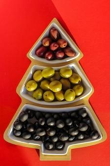 빨간색 배경에 크리스마스 트리 모양의 꽃병에 녹색, 검정 및 빨강 올리브. 새해 요리, 크리스마스 휴일 및 지중해 요리의 개념