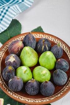 Fichi verdi e neri su un piatto di ceramica. foto di alta qualità