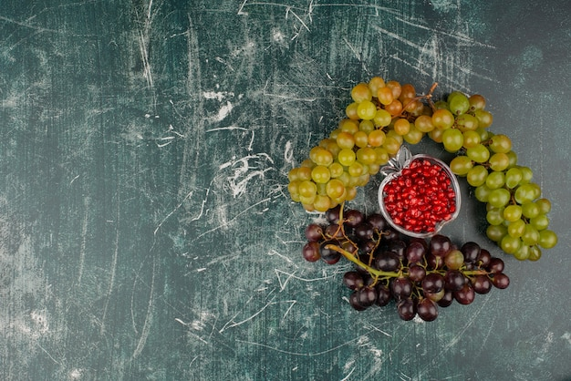 Green and black grapes with pomegranate seeds on marble surface.
