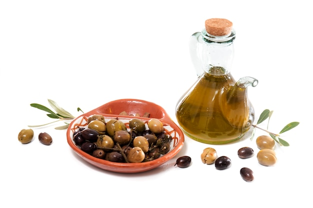 Green and black olives with olive oil bottle