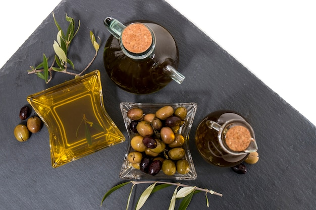 Green and black olives with olive oil bottles
