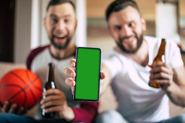 흥분된 젊은 수염 된 스포츠 팬의 손에 스마트 폰에 녹색 빈 화면. 베팅에서 승리