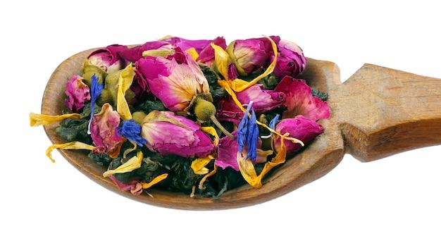 グリーンブレンドティー。白で隔離の木のスプーンで乾燥したバラの花と緑茶の葉。