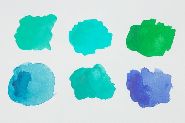 Зеленые, синие и аквамариновые пятна краски на белой бумаге