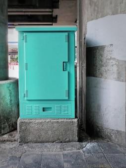 Зелено-синий шкаф электрического управления на углу улицы