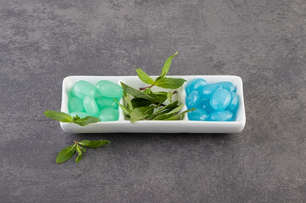Green and blue gums with mint leaves on white plate over grey surface