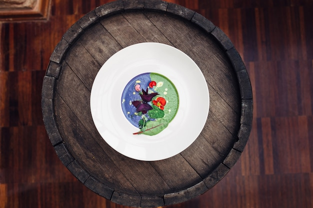 Green and blue soup served in white plate stands on the barrel