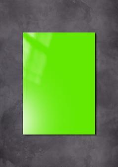 어두운 콘크리트 배경에 고립 된 녹색 책자 표지