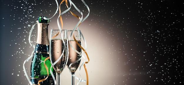 Зеленая бутылка шампанского, фужеры с крупным планом серебряных и золотых лент. праздничная композиция на темном фоне с подсветкой
