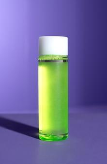 Зеленая бутылка косметического средства на фиолетовом фоне с жесткой тенью