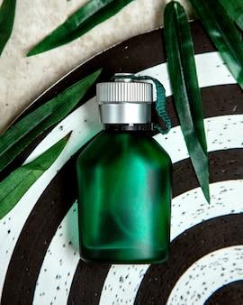 Bottiglia verde di profumo sul tavolo